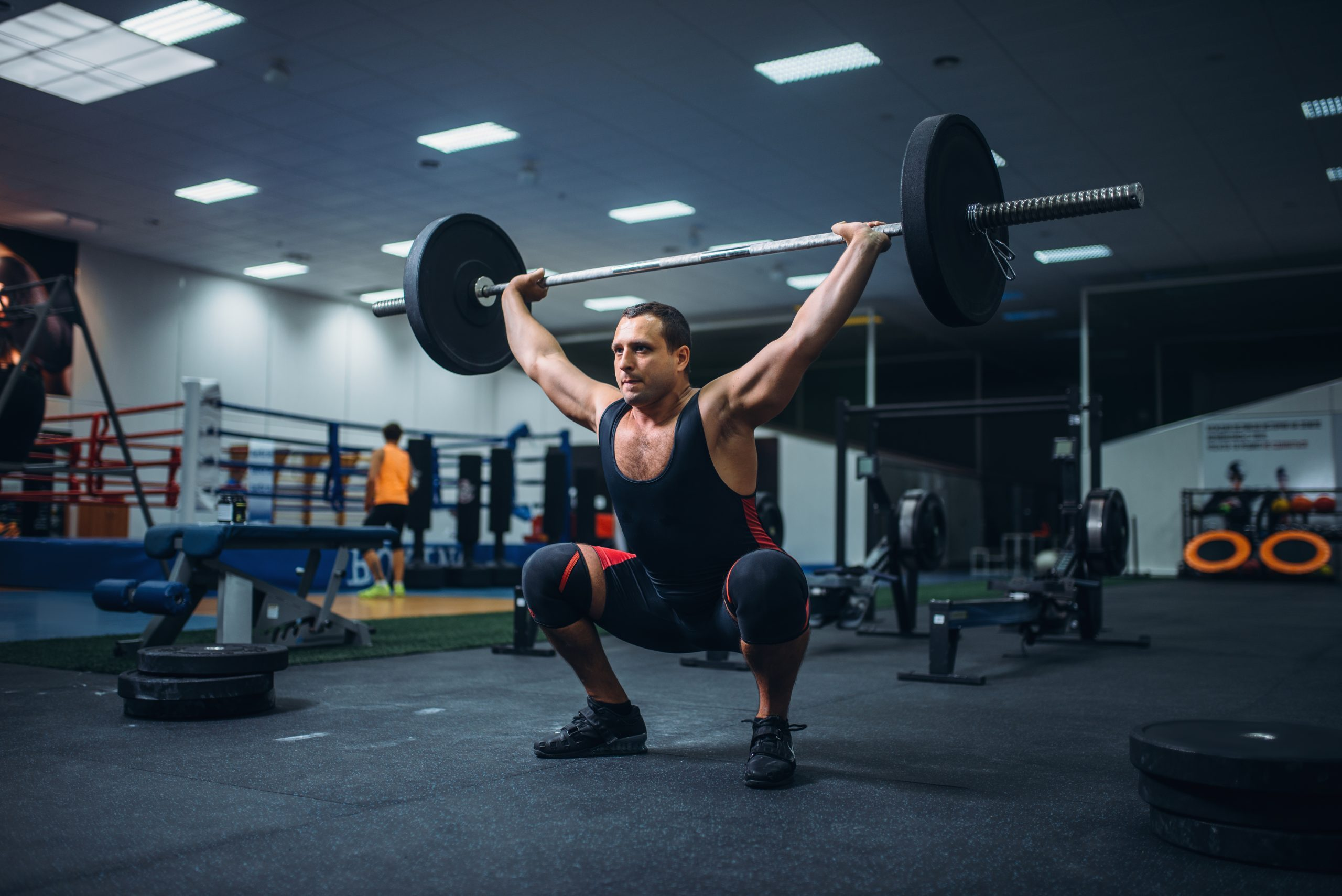 Strong male powerlifter doing deadlift a barbell in gym. Weightlifting workout, lifting training, athlete works with weight in the sport club